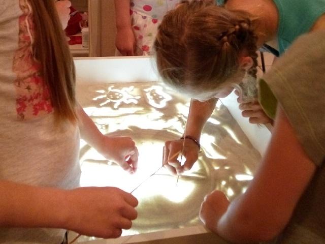 Дети рисуют на столе для рисования песком